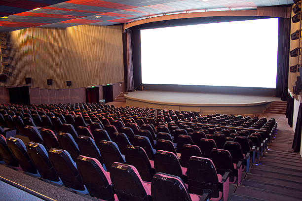 An empty cinema with blank white movie screen stock photo