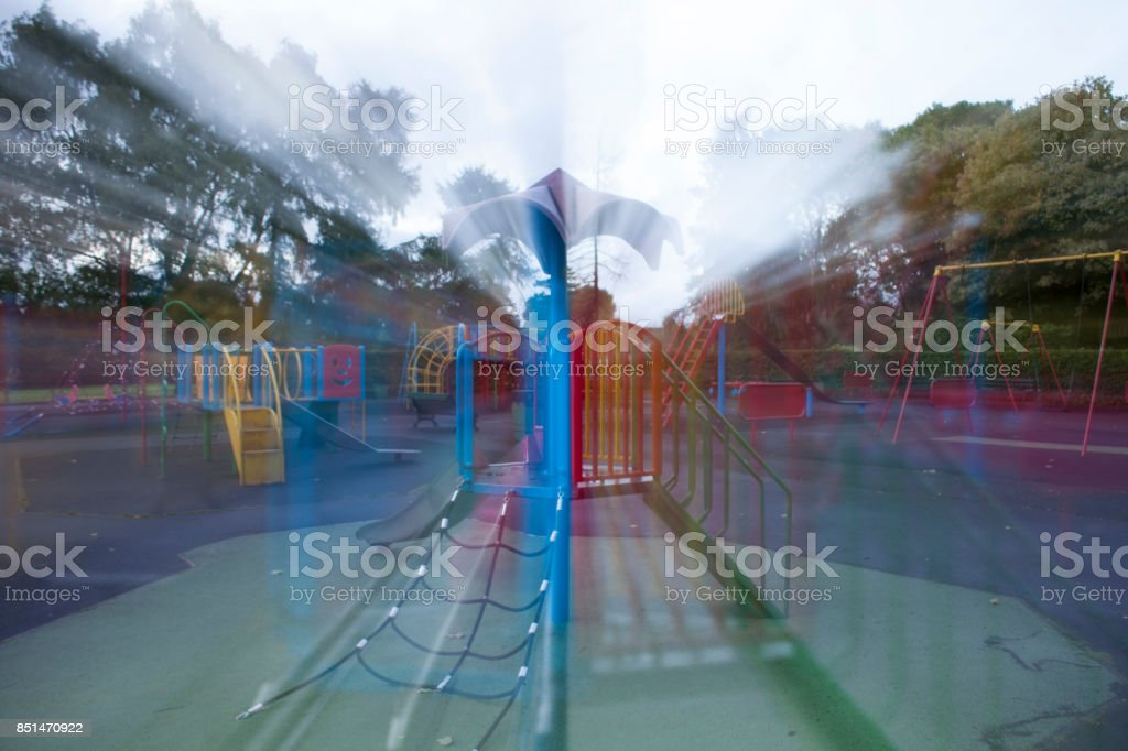 An empty Colourful children playground in the middle of busy par stock photo