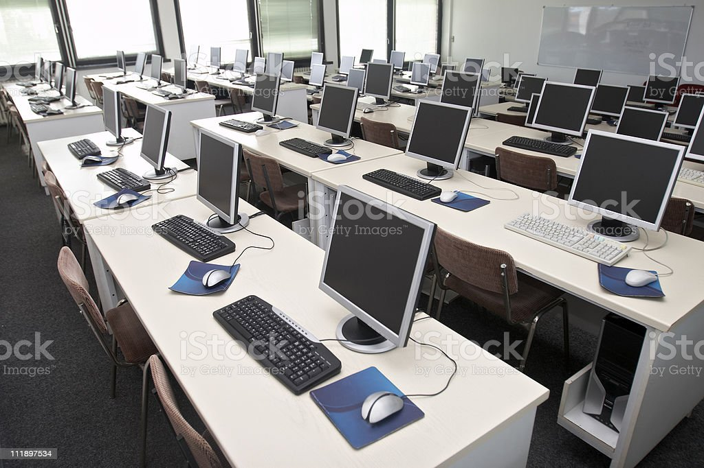 An empty computer training classroom with blue mouse pad stock photo