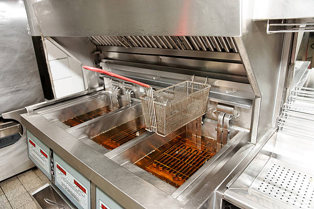 An empty deep fryer with oil in bins and baskets on top stock photo