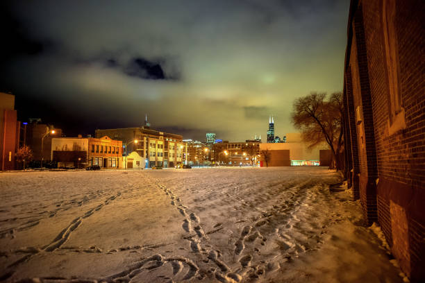 An empty deserted snow field with foot prints and the Chicago skyline at night stock photo