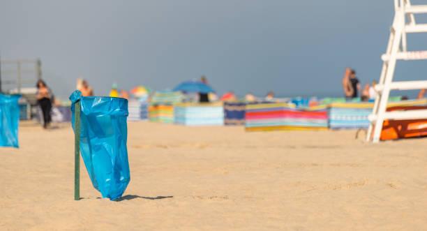 Eine leere Mülltüte am Strand an einem sonnigen Sommertag im Hintergrund Menschen, ein Strand-Bildschirm und ein Rettungsschwimmer-Ständer. – Foto