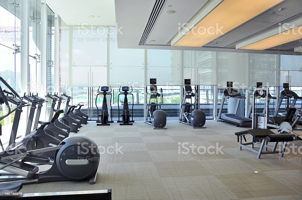 An empty gym room with rows of running machines stock photo