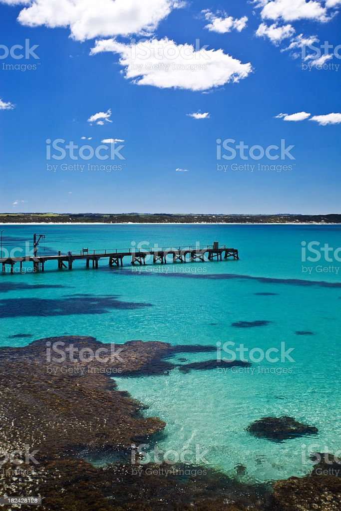 An empty jetty in a beatiful bay with blue skies  stock photo
