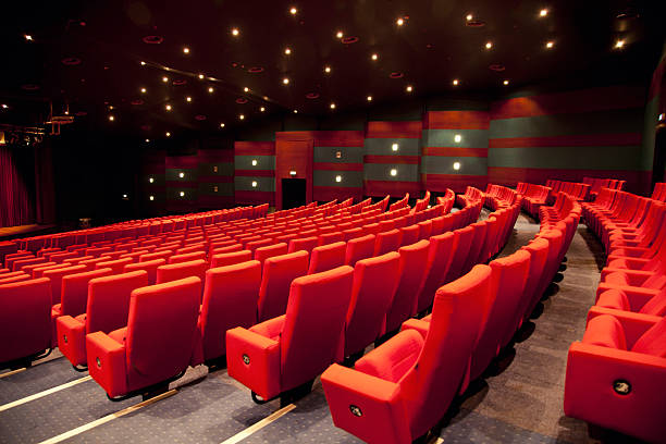An empty low lit theater with red seats in rows stock photo