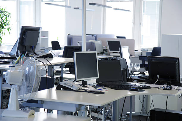 An empty office with desks and flat screen computers stock photo