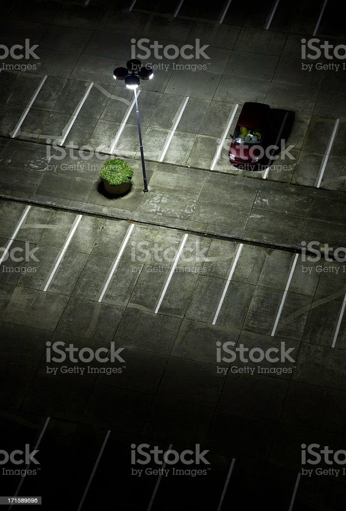 An empty parking lot at night with one red car stock photo