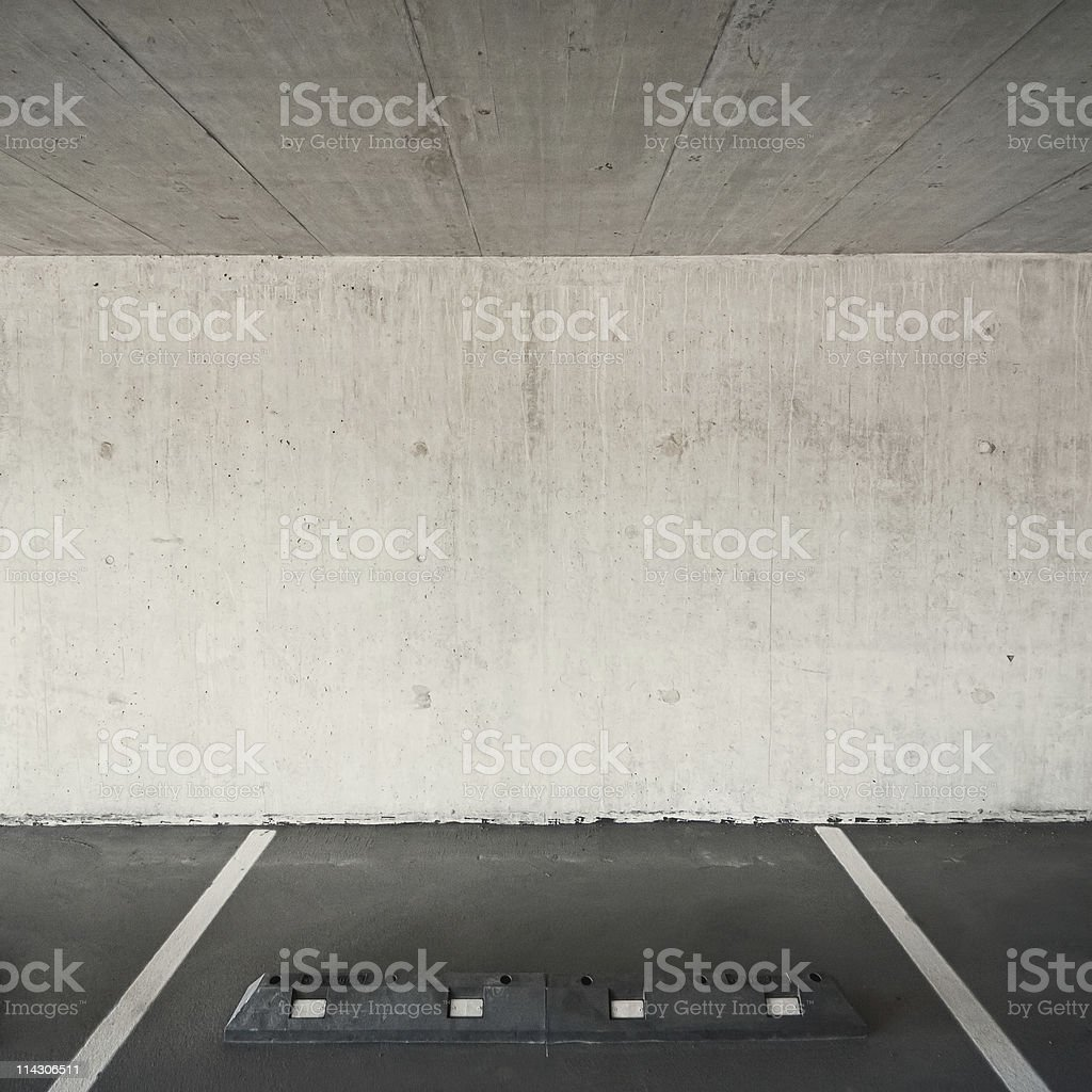 An empty parking space in an old white-walled parking lot royalty-free stock photo