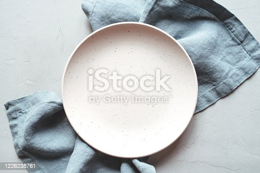 An empty plate and napkin on the gray background. Top view.