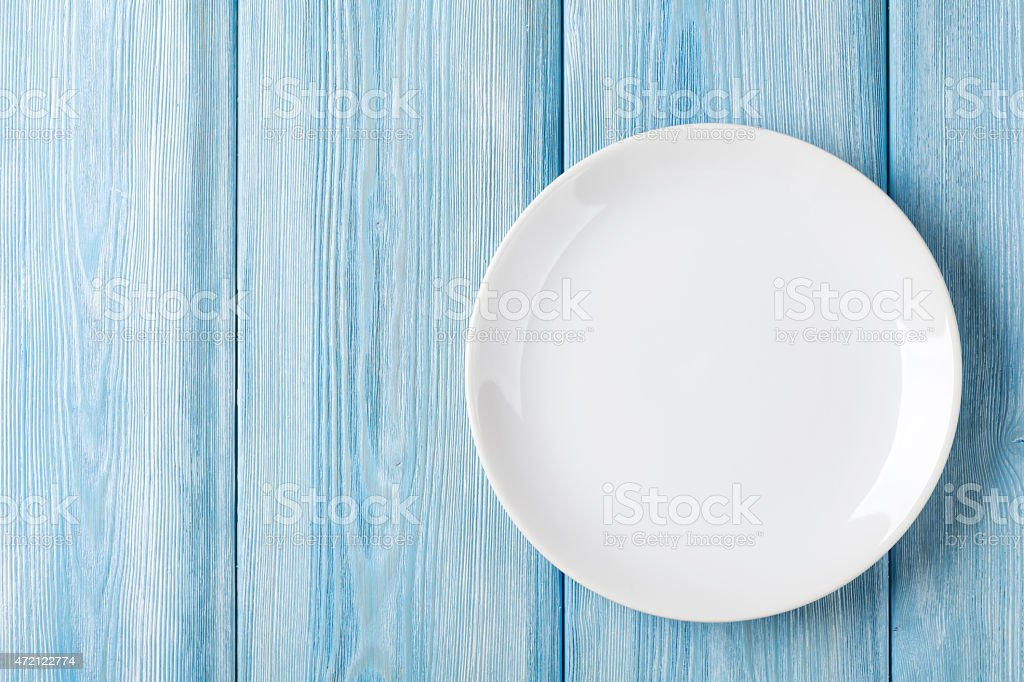 An empty plate sitting on a blue wooden background stock photo
