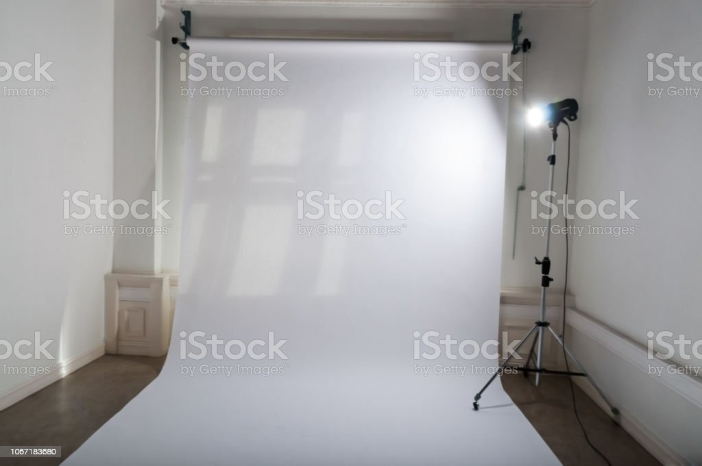 An Empty Professional Photo Studio With Clean And Simple Photographic Equipment Setup Of White Plain Paper Backdrop And A Brightly Lit Flash Spotlight On A Lamp Tripod In A Dimmed Atelier Stock