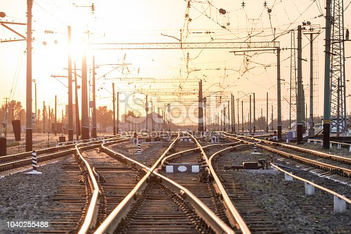 An empty railway sorting station or terminal with lots of junction, crossroads, semaphore showing red or green light, in a bright sunset light. The difficulty of finding the right way concept
