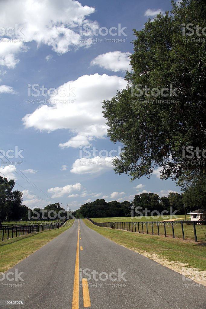 An empty road with yellow lines and a beautiful sky stock photo