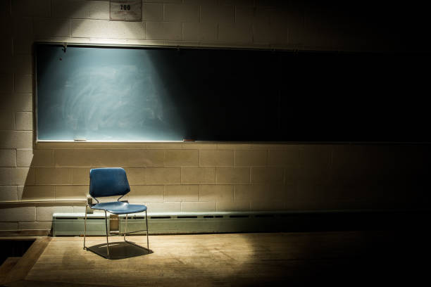An Empty School Chair in a Dark, Shadowy Classroom - in Front of a Chalkboard with a Single Beam of Light Overhead An Empty Chair in a Dark Classroom failure stock pictures, royalty-free photos & images