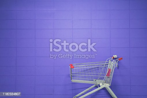 An empty shopping cart against a purple blank wall
