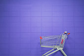 istock An empty shopping cart against a purple blank wall 1182334807
