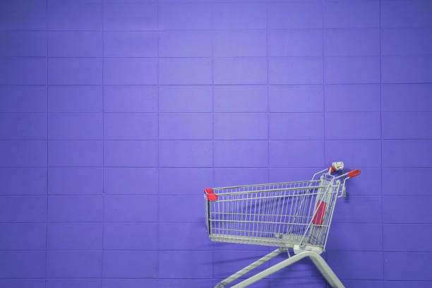 An empty shopping cart against a purple blank wall stock photo