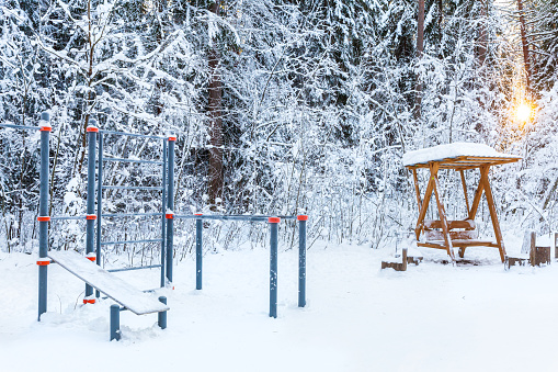 An empty sports ground in a winter park or forest against the backdrop of snow-covered trees. Infrastructure for sports, leisure, outdoor activities, healthy lifestyle.