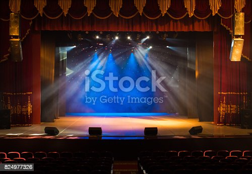 istock An empty stage of the theater, lit by spotlights and smoke 824977326