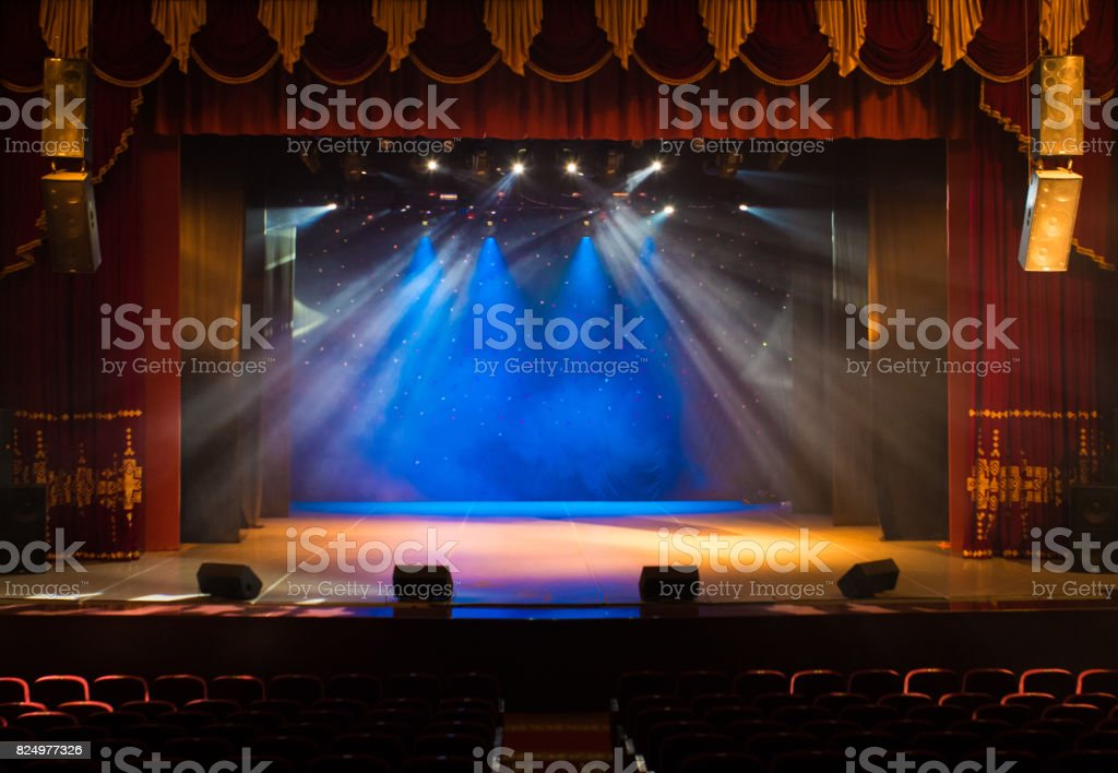 An empty stage of the theater, lit by spotlights and smoke stock photo