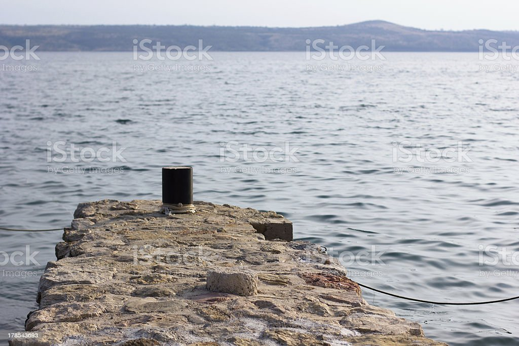 An empty stone dock on the sea. One tie down royalty-free stock photo