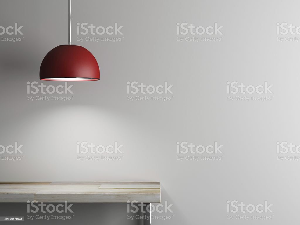 An empty table with a red lamp hanging above it stock photo