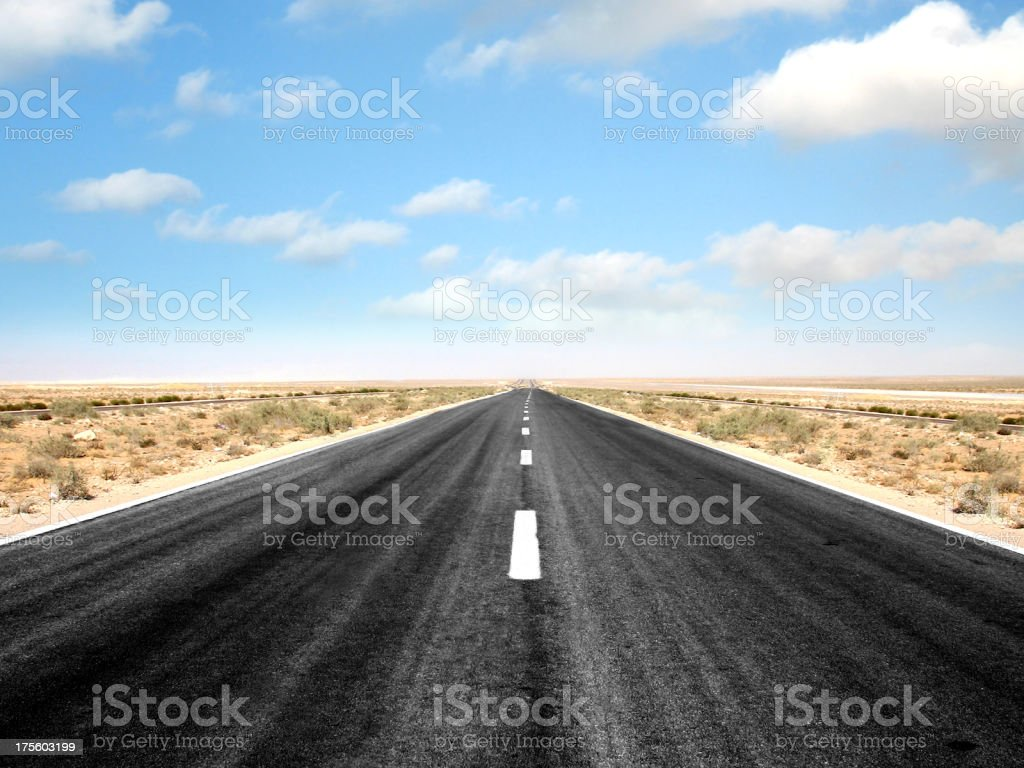 An empty two-lane highway in the middle of a desert stock photo