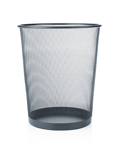 An empty waste paper basket in gray stock photo