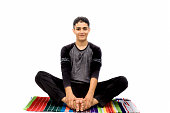 An energetic Young Caucasian teenager doing Bound Angle Pose or BAH-dah cone-AHS-anna pose practice isolated on white wearing black attire.