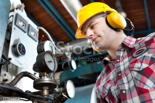 istock An engineer at work wearing a hard hat and ear defenders 177044519