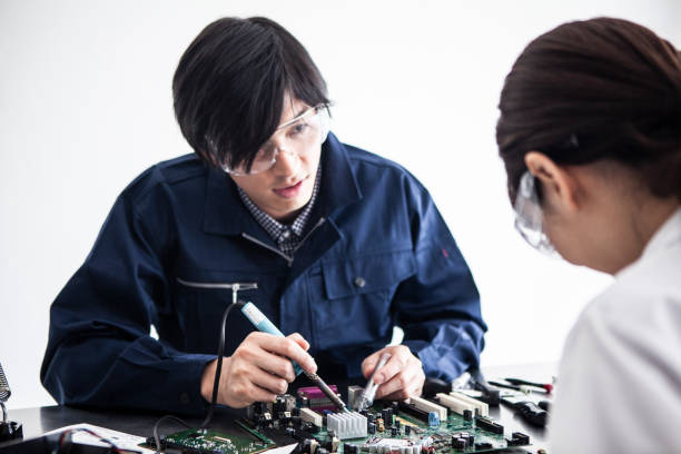 An engineer who assembles electronic components. stock photo