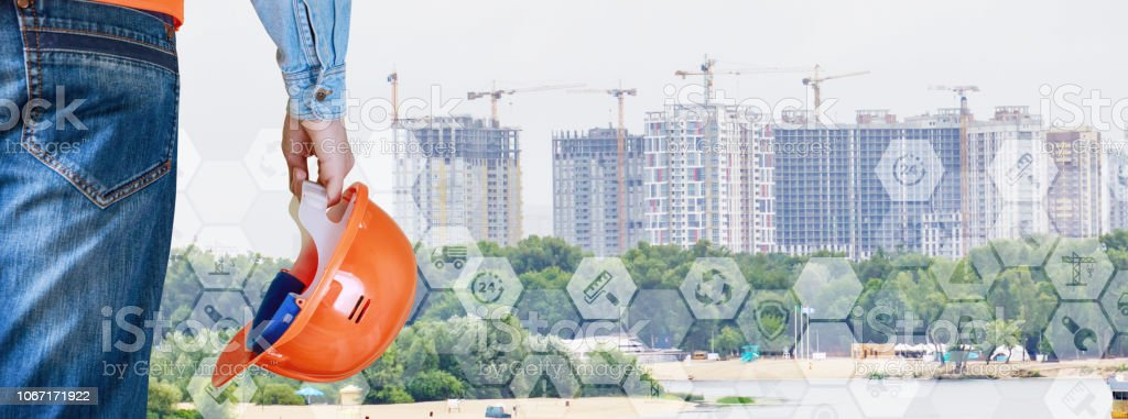 An engineer with a building helmet in his hand is standing opposite the set of city skyscrapers. stock photo