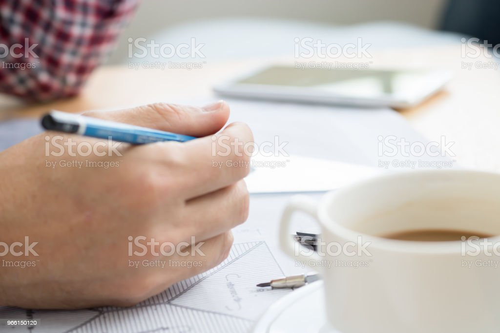 An engineer work for architectural project.With a cup of coffee,tools,drawing and white helmet on work table at home office.selective focus - Royalty-free Adulation Stock Photo