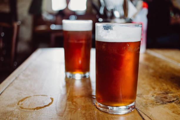 um pint de cerveja amarga cerveja inglesa sobre uma mesa de madeira em um pub no reino unido - ale - fotografias e filmes do acervo