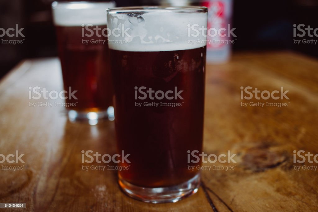 An english ale bitter beer pint on a wooden table in a pub in UK stock photo