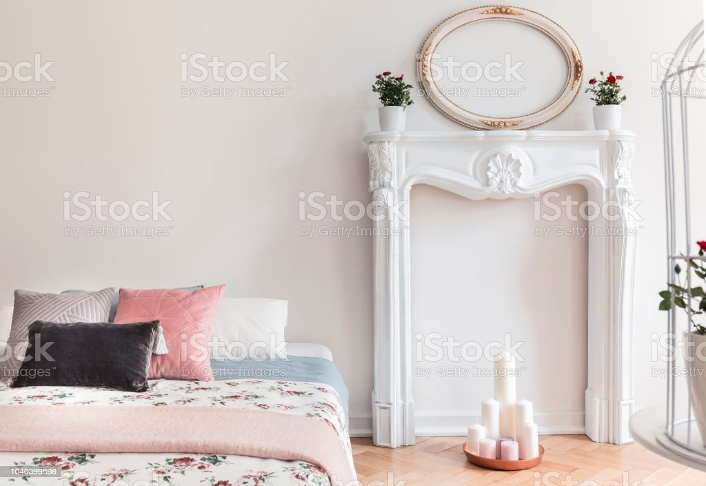 An English Style Bedroom Interior With Pastel Pillows And Rose