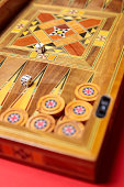 An entertaining game of backgammon on a red background. Checkers, cubes, handmade board