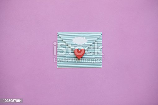 An envelope with a red heart for Valentine's Day or for Women's Day or for the wedding. A joyful message or letter. Festive concept in minimal style.