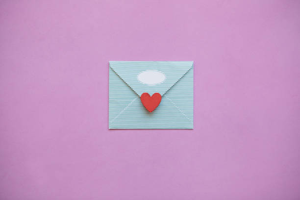 An envelope with a red heart. An envelope with a red heart for Valentine's Day or for Women's Day or for the wedding. A joyful message or letter. Festive concept in minimal style. sentimentality stock pictures, royalty-free photos & images