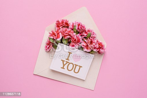 680461500 istock photo An envelope with pink flowers and a card I love you on a pink background 1128637118