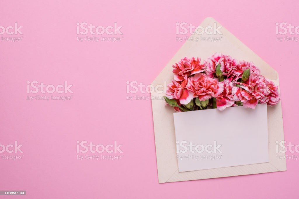 An envelope with pink flowers and a present card on a pink background...