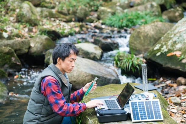 un ricercatore ambientale che monitora la qualità dell'acqua da un laboratorio sul campo ad energia solare - ambientalista foto e immagini stock