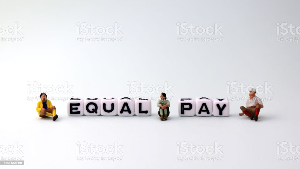An equal pay concept. EQUAL PAY text cube and three miniature people. stock photo