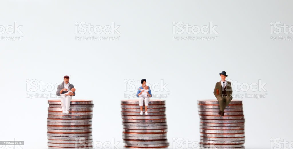 An equal pay concept. Miniature people sitting in the same height pile of coins. stock photo