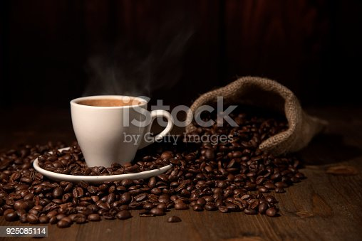istock An Espresso Coffee Cup  with smoke on wood table with Beans Jute Bags 925085114