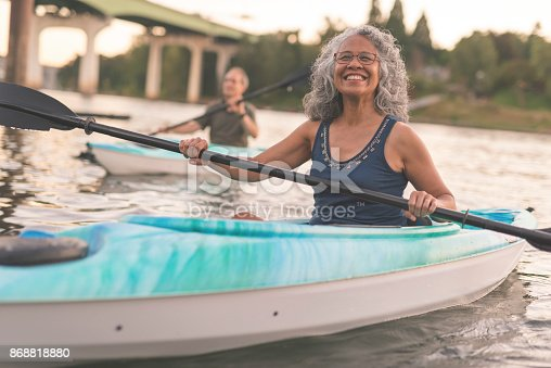istock An ethnic senior woman smiles while kayaking with her husband 868818880