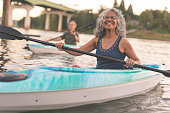 A mixed race senior couple is kayaking down a river together. The image's focus is on the elderly woman smiling in the foreground. She is Pacific Islander and has graying hair. Her husband is seen in a kayak in the background. In the distance behind the couple you can see the shoreline and a bridge. The happy couple are wearing casual clothing. It is warm outside.