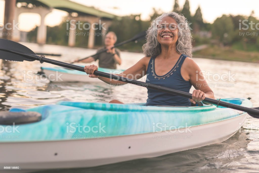 An ethnic senior woman smiles while kayaking with her husband stock photo