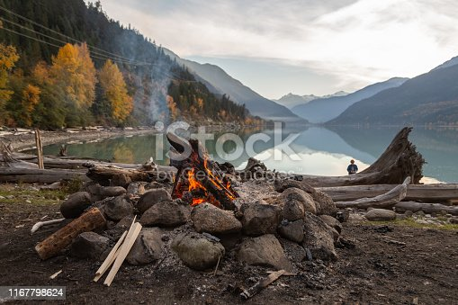 A campfire and kindling sit next to a rock and drift wood covered beach with the mountains and colourful fall leaves reflecting in the calm waters of Lillooet Lake in the background as the sun sets.