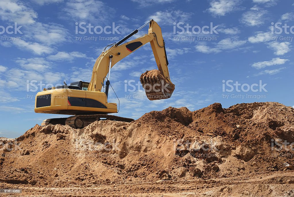 An excavator digging up dirt in a sand pit stock photo